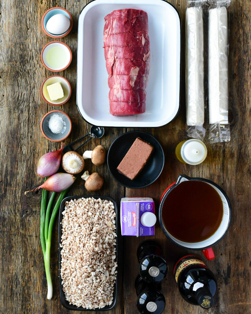 A top down image of ingredients needed for a beef wellington recipe.