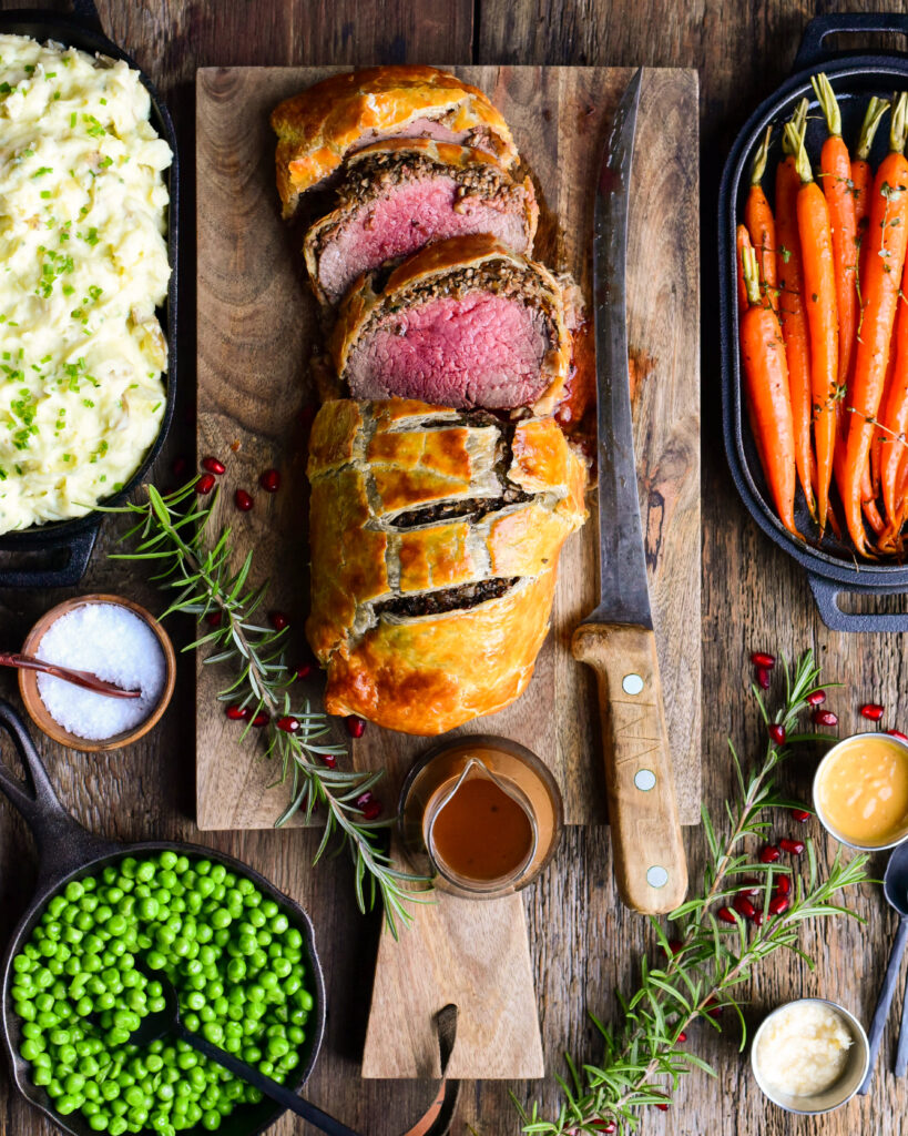 Top down image of a medium rare sliced Beef Wellington on a cutting board with a large carving knife and sauce. Carrots, peas and mashed potatoes surround the beef.