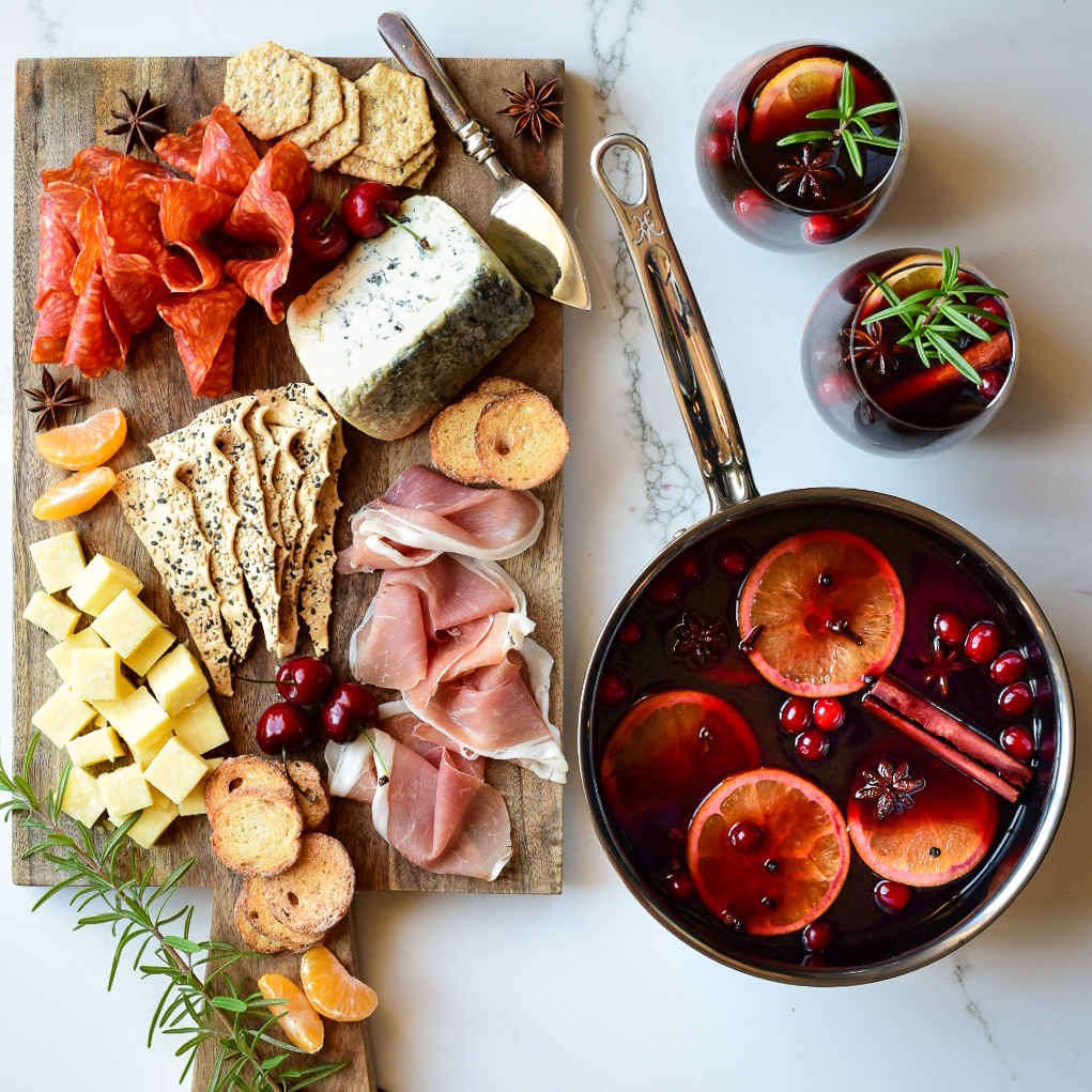 Top down image of a charcuterie board and a simmering pot of mulled wine and two glasses garnished with oranges, star anise, cinnamon and cranberries.