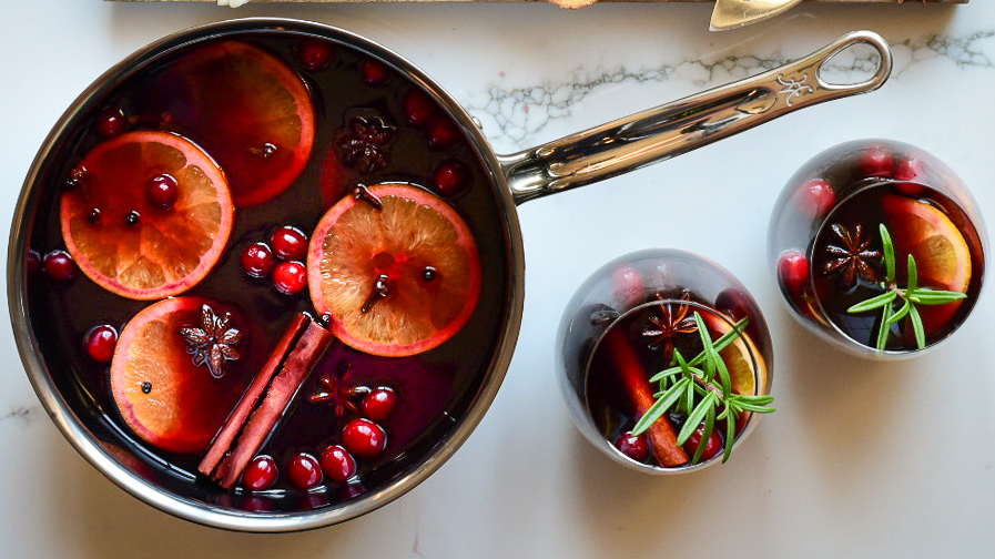 Top down image of a simmering pot of mulled wine and two glasses garnished with oranges, star anise, cinnamon and cranberries.