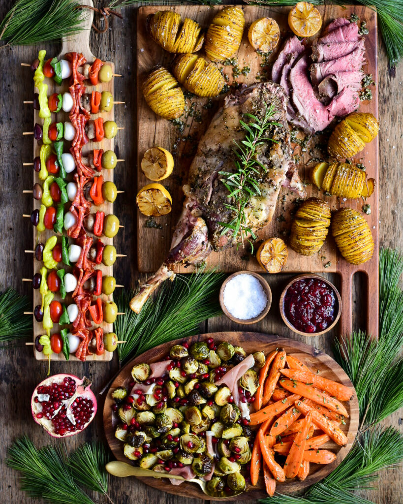 Top-down image of a sliced roasted leg of lamb on a cutting board with hassle back potatoes and lemons. As well in this image is a narrow board of antipasto skewers and a platter of roasted carrots and brussels sprouts with pomegranate arils.