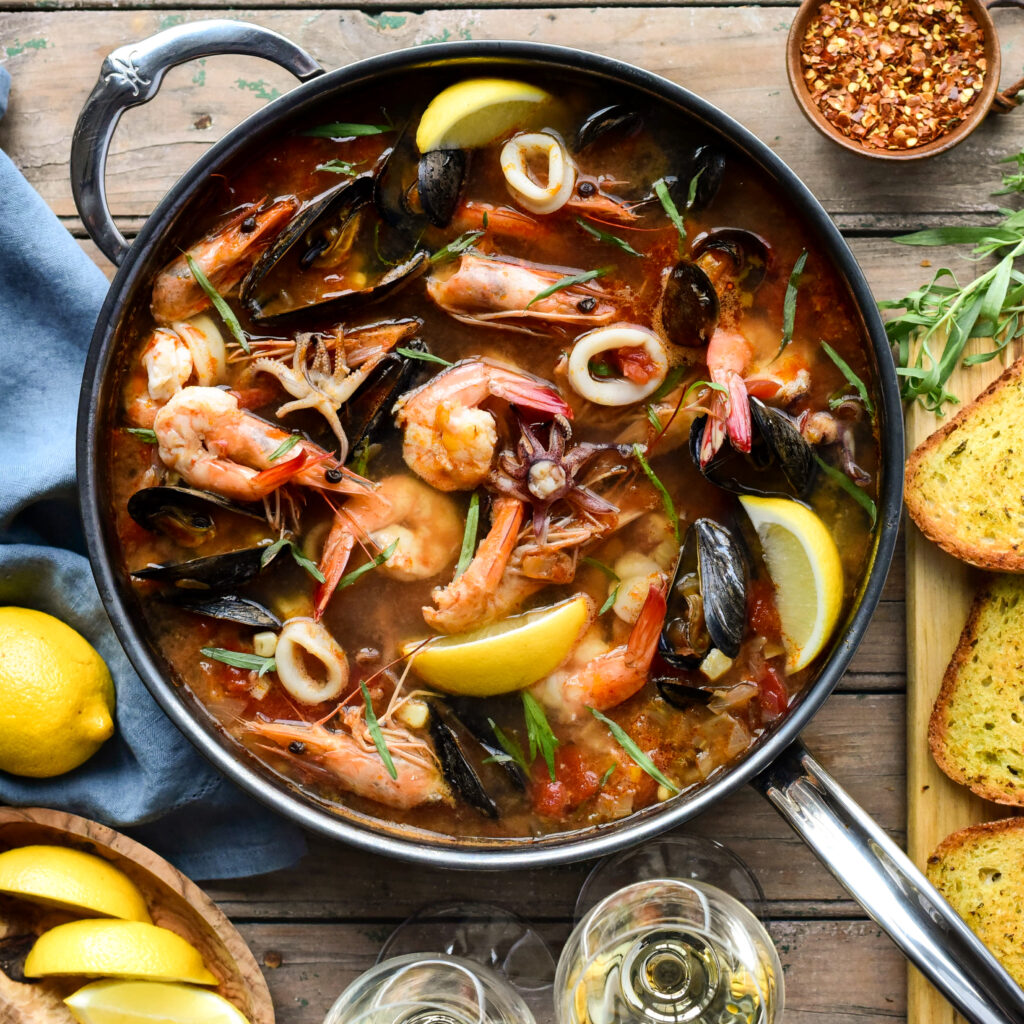 Top down image of a fish stew filled with mussels, shrimp, calamari, lemons and surrounded with wine glasses and garlic toast.
