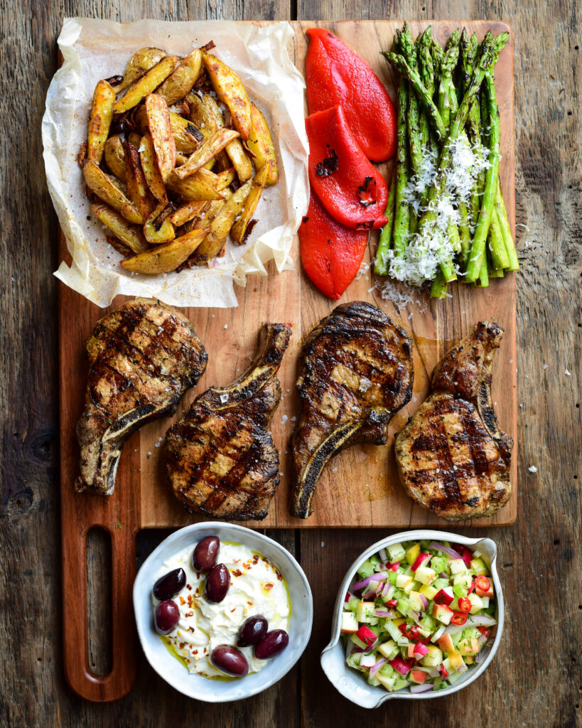 Four pork chops with great grill marks, roasted potatoes, grilled red peppers, asparagus, hummus and apple slaw
