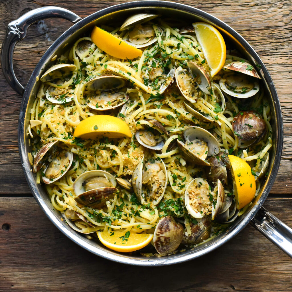 Top down image linguine, clams  and lemons with parsley in a pan.