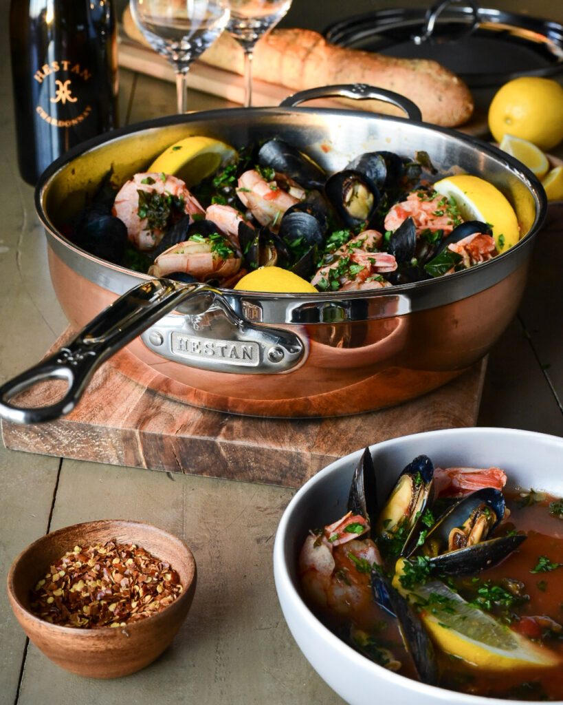 A beautiful copper pot filled with mussels, shrimp, lemons and kale. This pot is surrounded by a bowl filled with this soup, a wooden bowl of chili peppers, wine, wine glasses, lemons and a loaf of bread.