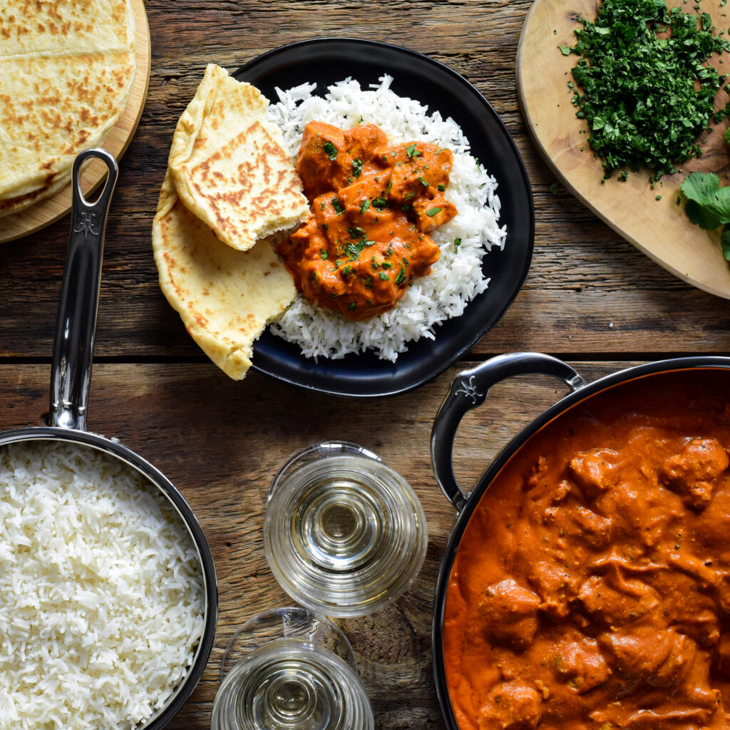 A plate of Chicken Tikka Masala served over rice with naan.  Surrounding this plate is the pot filled with chicken, a pot full of rice, wine glasses and chopped cilantro.