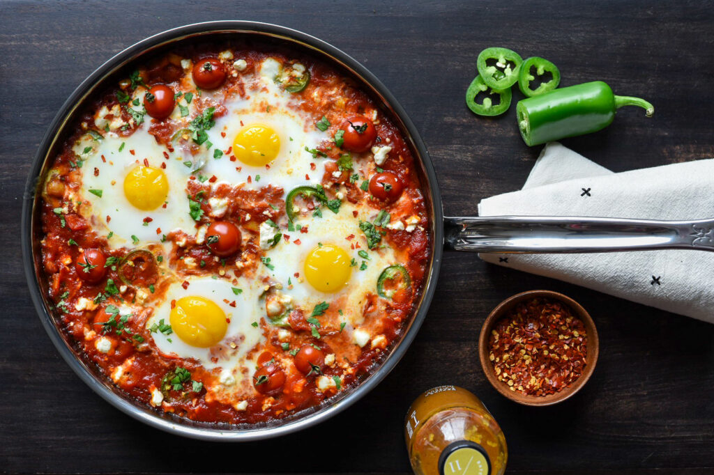 A skillet filled with spicy Shakshuka. Four sunny side up eggs are poaching in a tomato sauce with herbs, veggies and feta cheese.