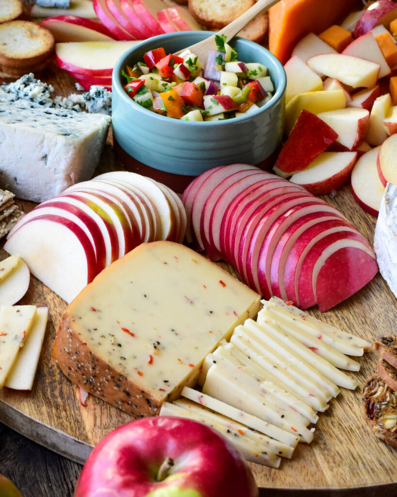 A close up image of an apple and cheese board, featuring slices of smoked habanero cheese and semi-circles of apples.