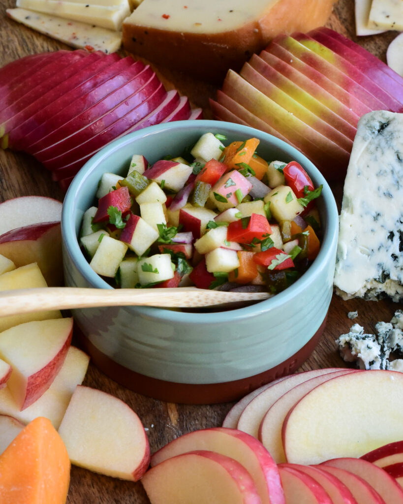 A close up image of an apple and cheese board, featuring a bowl of apple salsa.