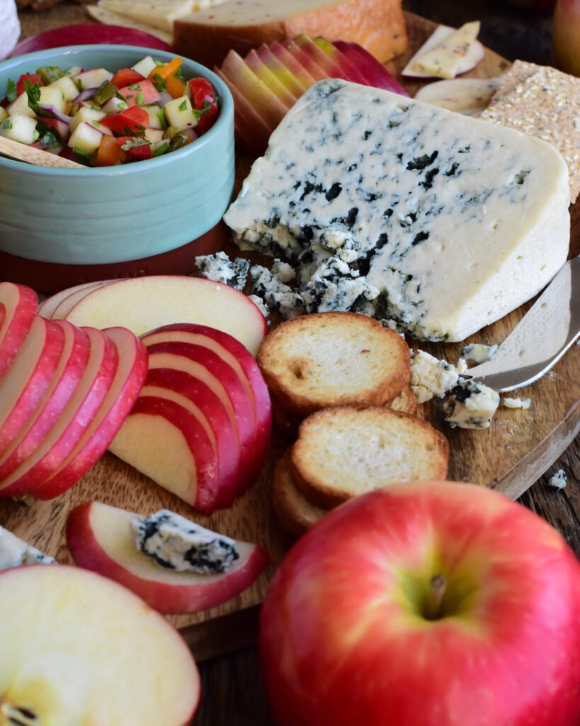 A close up image of an apple and cheese board, featuring a wedge of blue chees and semi-circles of apples.