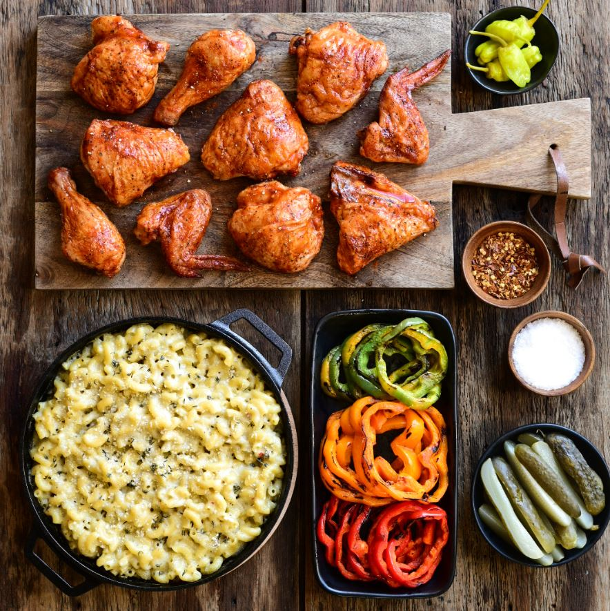 A cast iron dish with macaroni and cheese, a cutting board with chicken, a dish of roasted peppers, pickles and s&p.