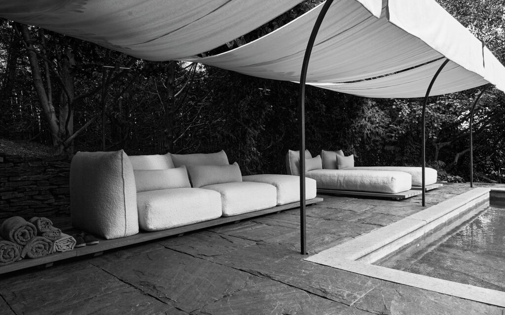 Black and White photo featuring sofas under a canopy outside.
