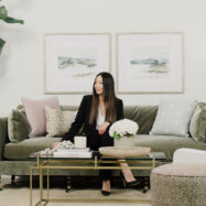 Woman sitting on olive green couch in a designer living room