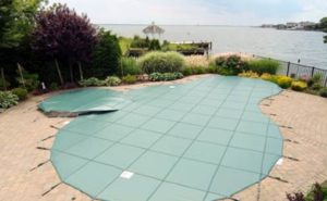 Green pool cover over an elegant pool
