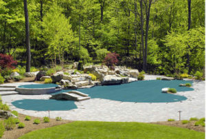Green pool cover atop an exotic pool