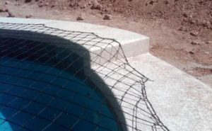 Black pool safety net attached to a concrete deck