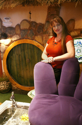 """SE-COMMERCIALCENTER--Paula Sadler, owner of A Harmony Nail Spa and president of the Commercial Center Business Association, stands next to a giant purple hand chair, while a spa foot bath runs in the foreground. The """"hobbit hole"""" (background) is one of the features of the spa.  Commercial Center is located at 953 E. Sahara Ave. 6/6/08 View photo by Dale Dombrowski"""
