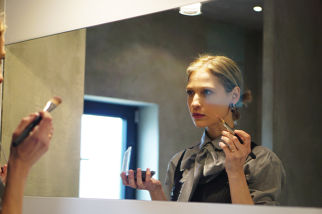 Victoria Onken is putting on make up in a grey Mila&James shirtdress with a bow