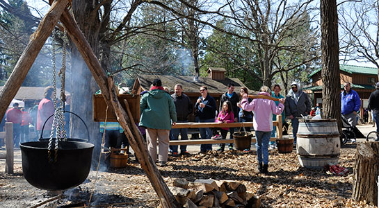 People on the grounds and maple kettle