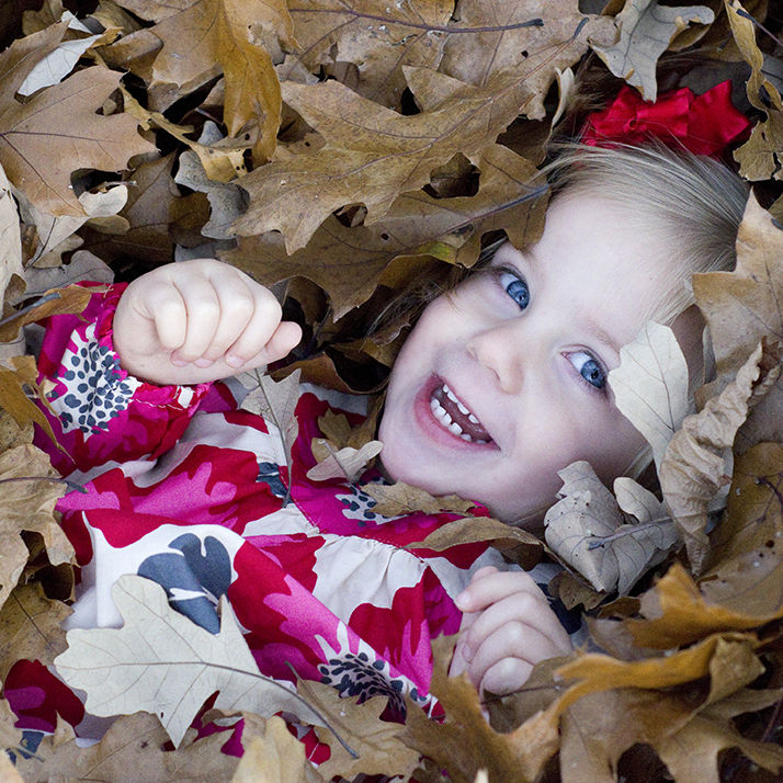 cute little girl is buried and surrounded by Fall leaves