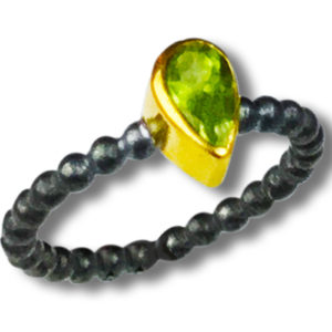 Prosperity pear shape Peridot. Set in 22kt gold and heavy black oxidized silver. Please note: The black oxidation finish will eventually lighten in the upper exposed areas.