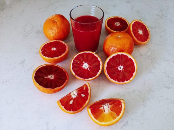 Blood Orange Juice with an array of oranges