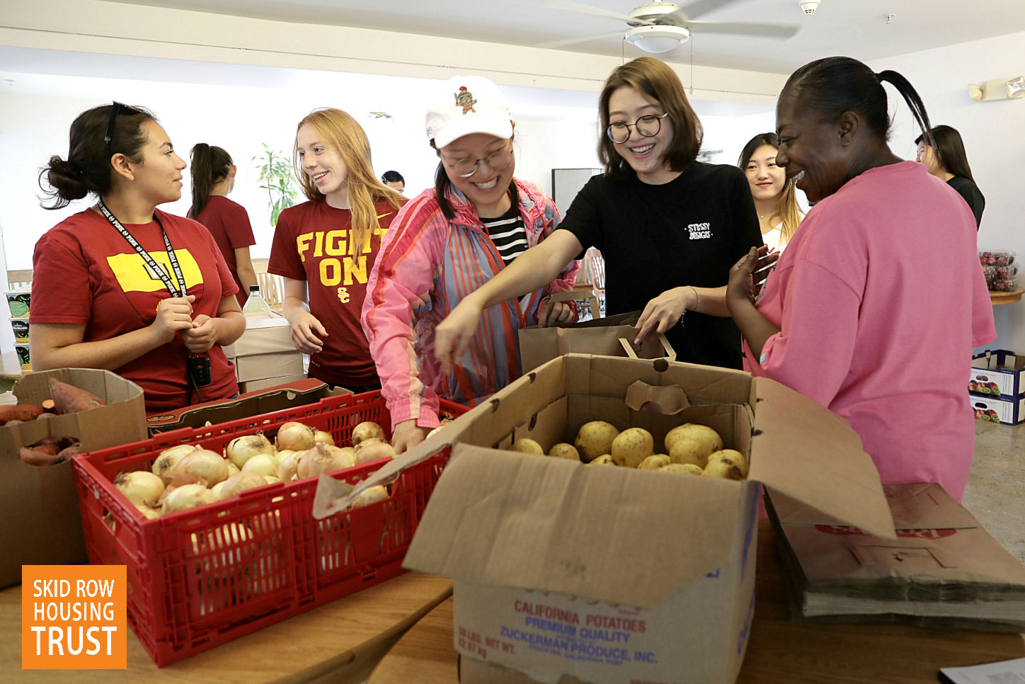 Student volunteers from USC set up a mini farmer's market in the community kitchen at the Abby Apartments. Residents were provided grocery bags and fresh produce for free.