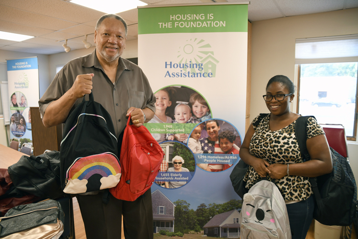 Barnstable Sunrise Rotary Club Past President Billy Roberts and Club President Nefertiti Holliday with the backpacks the club donated for Housing Assistance clients in need.