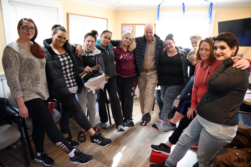 Angel House clients show off the sneakers they received from the Osterville Men's Club.