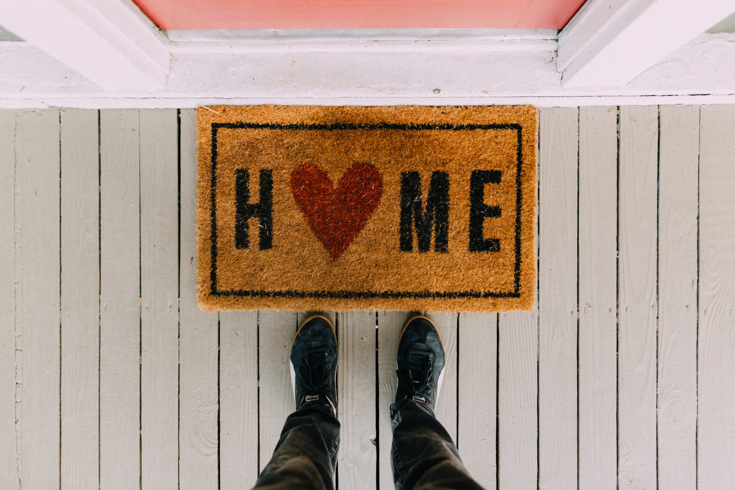Welcome Home Mat stock photo with feet in front of the mat.