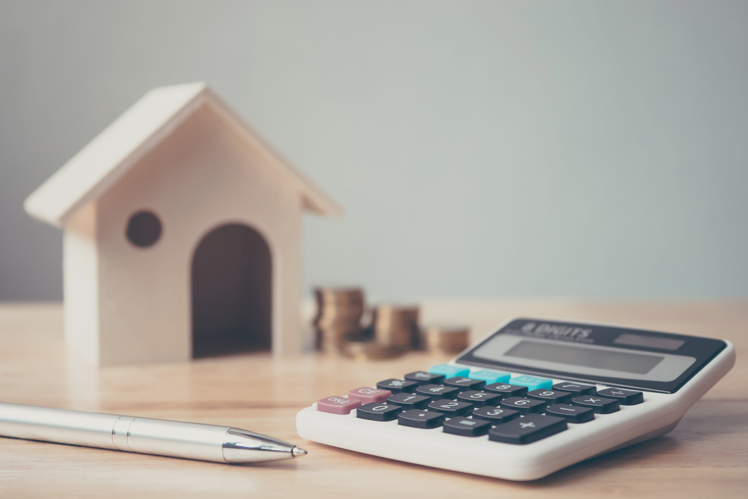 Stock photo of calculator with wooden house and coins, stack, and pen