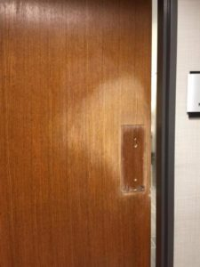 A restroom door with the color and finish worn off down to the wood