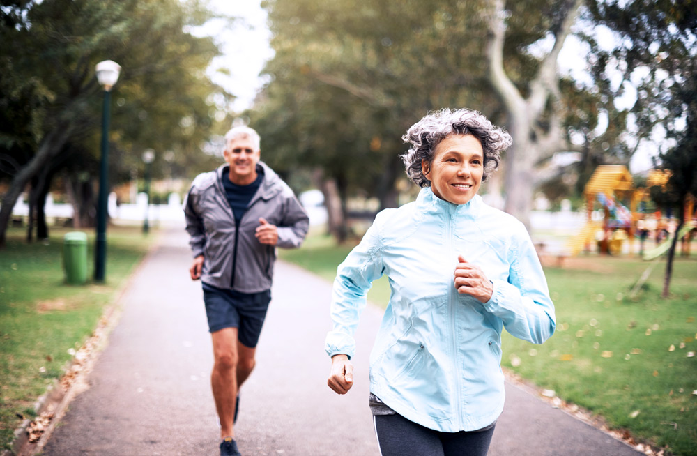 Two people jogging in a park after effectively managing their sports injuries