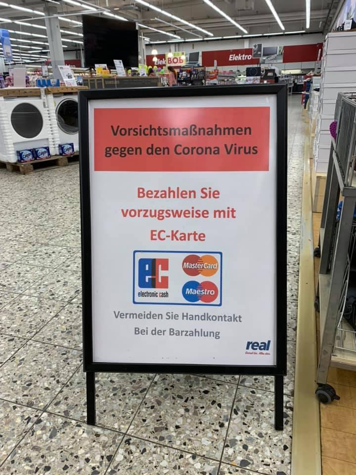 Cartel en una tienda de Alemania que pide tomar precauciones por la crisis del coronavirus y disminuir el contacto en favor de pagar con tarjeta.