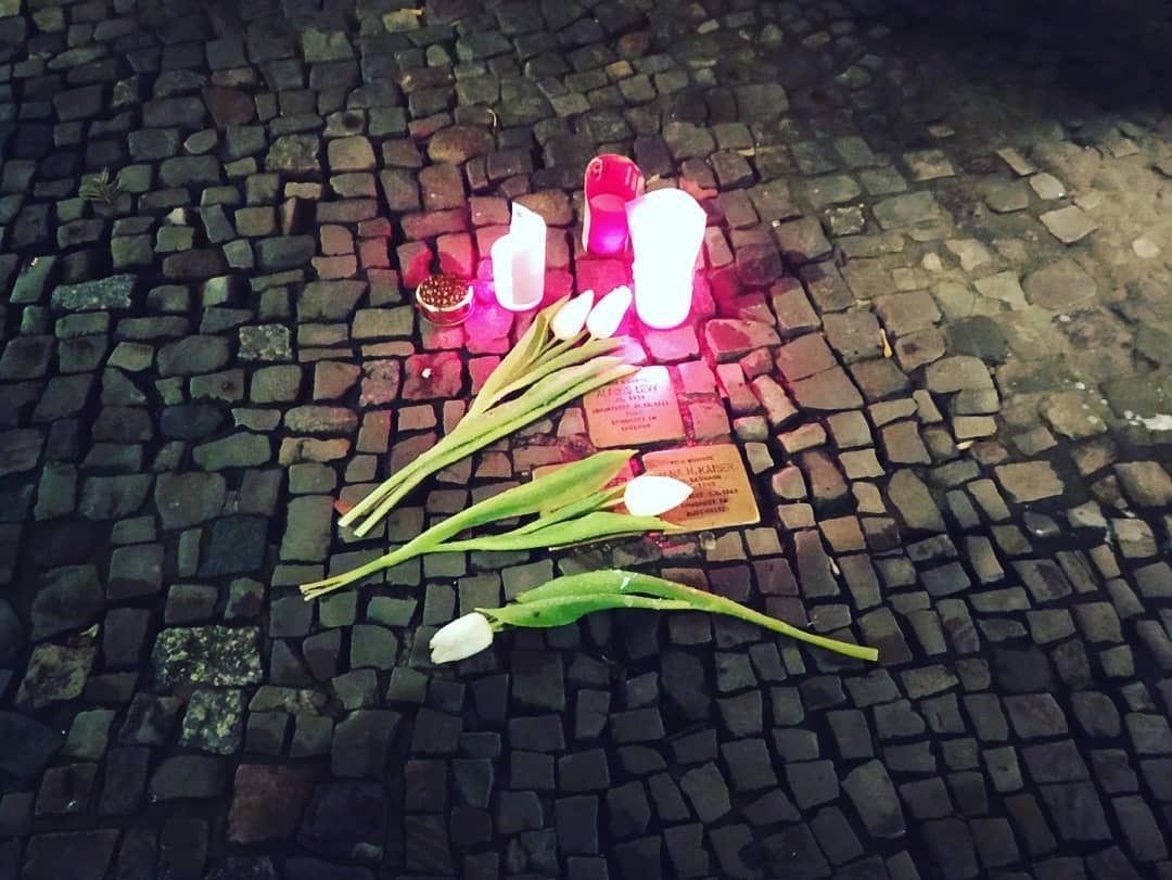 People leave candles in remembrance of those killed by Nazism on the plates of the German artist Guter Demnig, Stolpersteine.