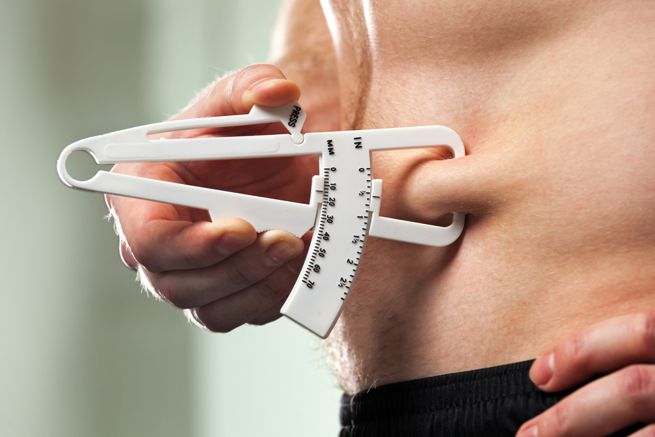 Man is measuring his body fat with calipers.