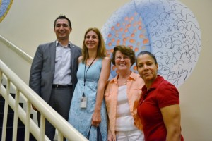 (From bottom right) Production worker Jeannette Vasquez, Salvona HR Manager Joan McCormack, NJ Department of Labor's Iliana Ivanov, and RTWNJ's Daniel Lim pose in front of a graphic illustration of one of Salvona's encapsulation technologies.