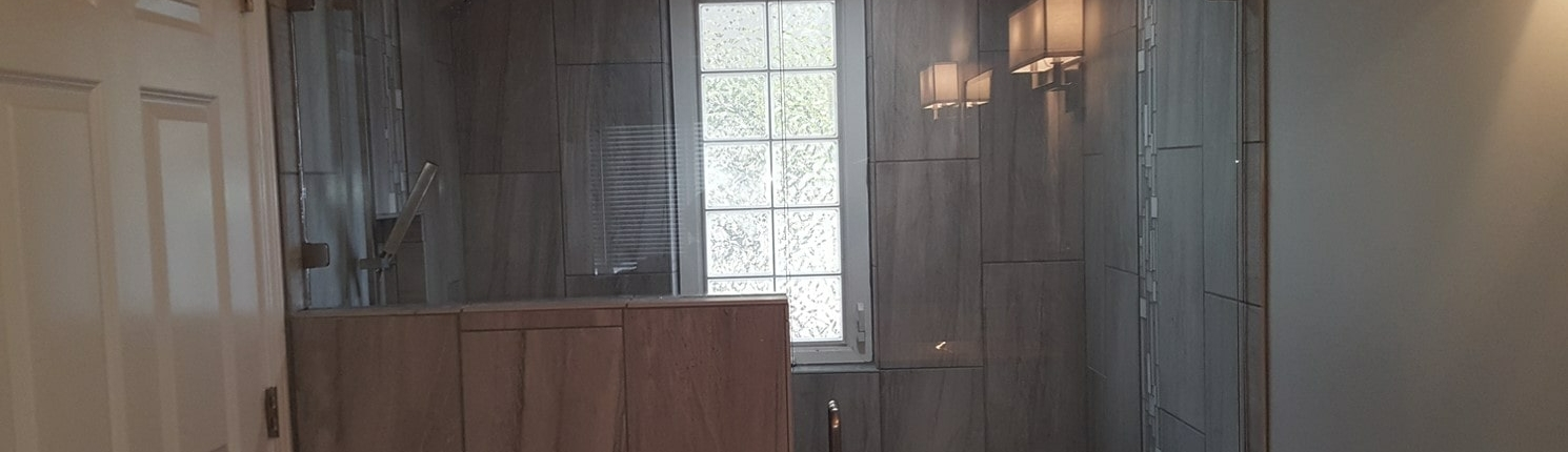 Bathroom with tile gray with half wall and glass shower door