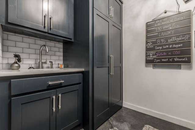 Keener laundry room with new dark gray cabinets and glass tile