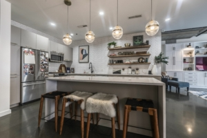 Condo kitchen with new lighting and bright white tile