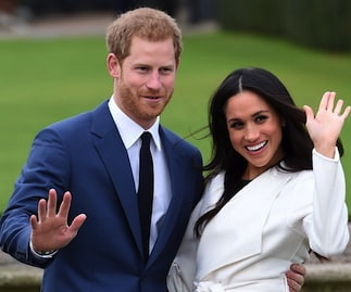 A happy Prince Harry with Meghan Markle on his arm in front of a long lawn