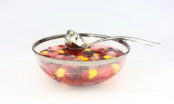 Bowl of punch with fruit and ice and with spoon