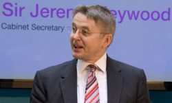 Lord Jeremy Heywood (deceased) in front of a banner saying that he was Cabinet Secretary