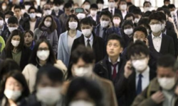 Crowded Japanese street scene with one foreigner without a mask and one nervous looking Japanese