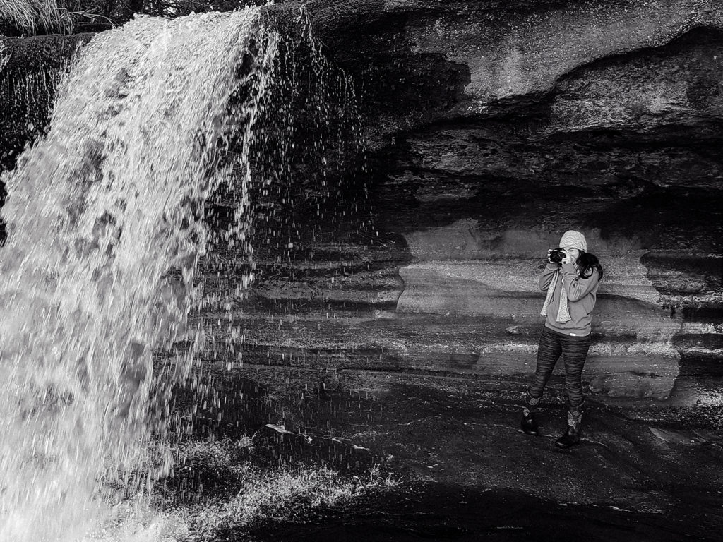 Ashley McMath taking a photo under a waterfall at Sandcut Beach Sooke BC