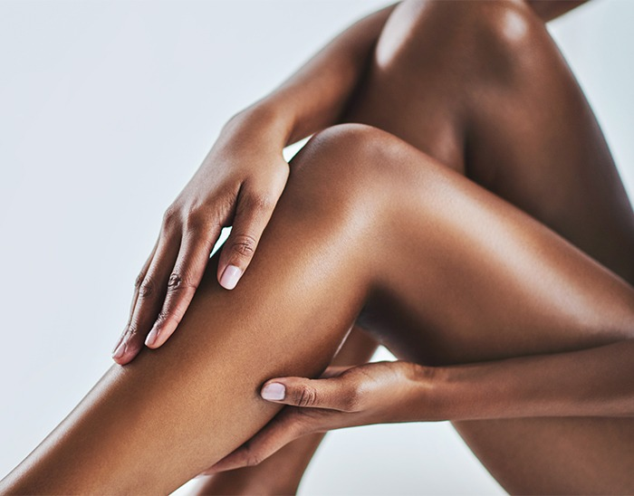 Cropped shot of a young woman caressing her legs, hairless