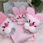 Three pink cloth rabbits with pearl eyes
