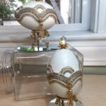 Two jeweled eggs. One at the bottom on top of a reflective sliver stands, the other sitting atop a glass jar.