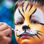 A bow having his face painted with yellow and black animal design.