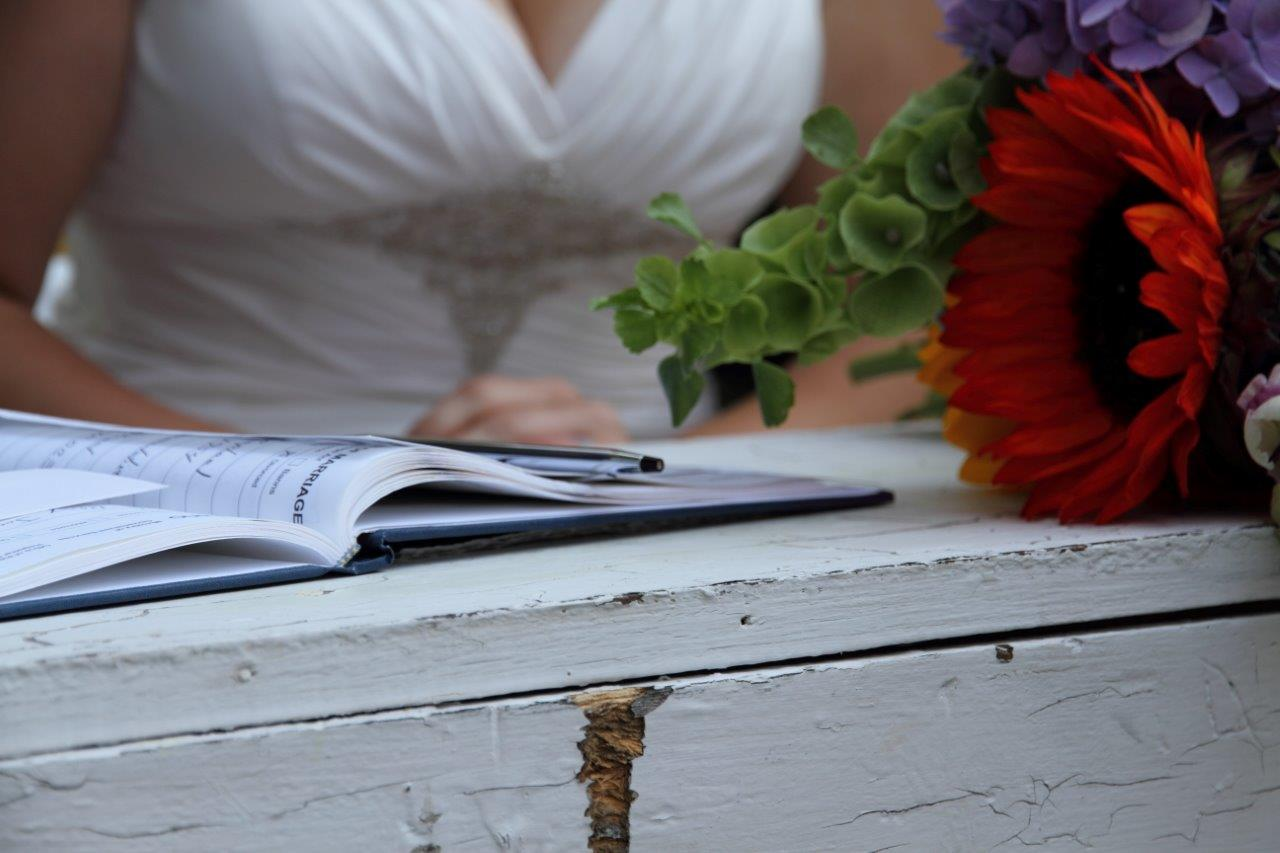 A bride signs the wedding certificate